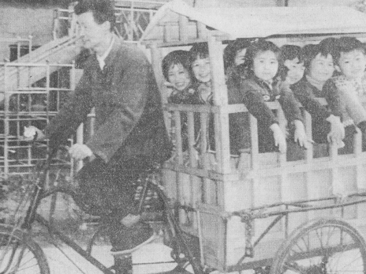 1987 A CESO client in Shanghai gives a group of happy children a ride to school